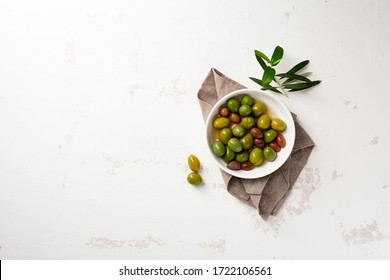 Overhead view of green pickled olive in white bowl and olive plant on white surface
