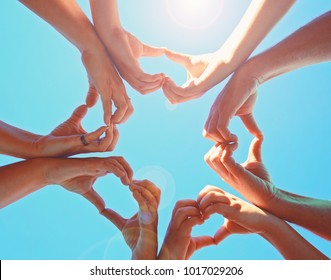 overhead view of a group of people making heart shapes with their hands directly below the sun with a lens flare toned with a retro vintage instagram filter