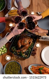 Overhead view of the hands of a group of young adult multi-ethnic male and female friends sitting at a table at home set for Thanksgiving dinner making a toast with glasses of red wine