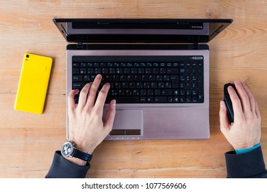 Overhead view of hands on a laptop and a wireless mouse by a yellow smartphone on a wooden surface