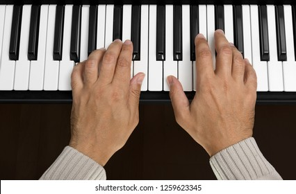Overhead view of hands playing a piano keyboard chord of A