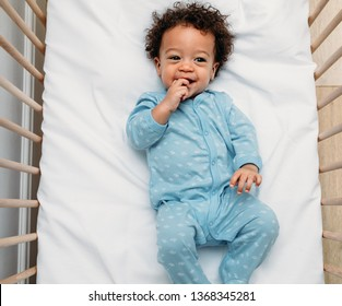 Overhead view of a happy baby boy lying in a crib wearing pajamas