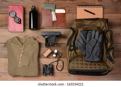 Overhead view of hiking gear laid out for a backpacking trip on a rustic wood floor. Items include, Backpack, gloves, sweater, camera, film, binoculars, passport, wallet, canteen, compass, money,