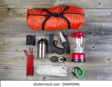 Overhead view of hiking gear and personal protection, pistol and knife, placed on rustic wood