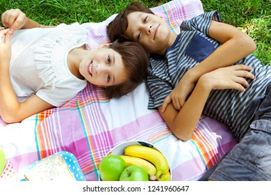 Overhead view of hispanic brother and sister children laying on picnic blanket looking smiling with healthy food, outdoors. Healthy fruit eating, colorful fun, leisure recreation lifestyle.
