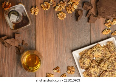 Overhead view of homemade chocolate walnut cookies with ingredients and a bottle and glass of scotch whisky on a dark rustic wood table. Open space in center for logo or text.