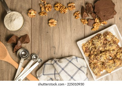 Overhead view of homemade chocolate walnut cookies with ingredients and kitchen utensils on a light rustic wood table. Open space in center for logo or text.