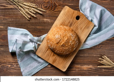 Overhead view of homemade wheat bread on wooden cutting board