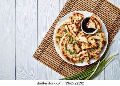 overhead view of hot Chinese green onion Pancakes on a platter with soy sauce on a white wooden table, view from above, flat lay