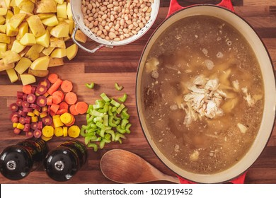Overhead view of the ingredients used to make homemade chicken and white bean soup.  Ingredients include sliced carrots, celery, potatoes, and white beans.  Homemade chicken soup stock is in the pot.