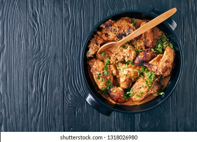 overhead view of Kuku Paka, Kenyan chargrilled Chicken in creamy spicy Coconut Sauce in a earthenware saucepan on a black wooden table, view from above, close-up, flatlay, copy space