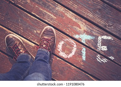 overhead view of legs and feet with shoes spelling out the word vote on a wooden deck toned with a retro vintage instagram filter