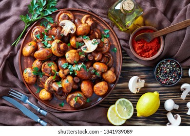overhead view of lightly fried champignons, Champinones Al Ajillo on an earthenware plate on an old rustic wooden table with brown cloth and ingredients, traditional spanish party food, flatlay