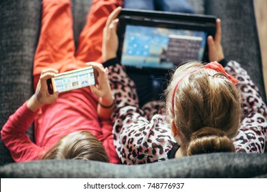 Overhead view Little girls children kids using phone tablet computer playing games