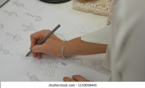 Overhead view looking down jewelry designer in studio sketching out designs