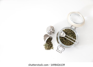 Overhead view of loose leaf green or herbal tea in a jar and mesh tea infuser with spoon on white background. Showing tea preparation