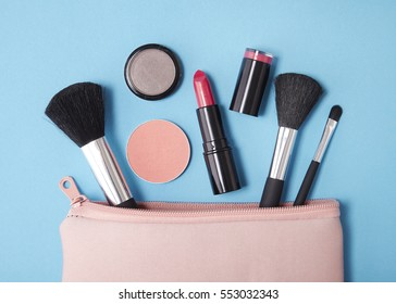 Overhead view of make up products spilling out of a pink cosmetics bag on to a blue background