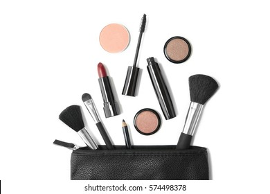 Overhead view of make up products spilling out of a black leather cosmetics bag, isolated on a white background