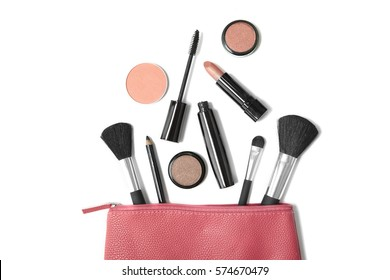 Overhead view of make up products spilling out of a pink leather cosmetics bag, isolated on a white background