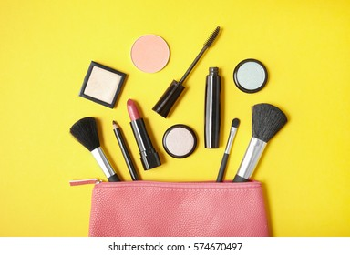 Overhead view of make up products spilling out of a bright pink cosmetics bag, on a vibrant yellow background
