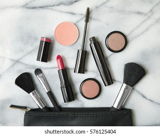Overhead view of make up products spilling out of a black cosmetics bag, on a white marble counter top background