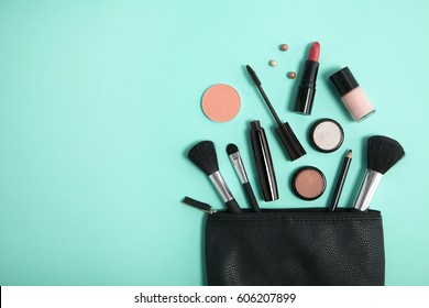 Overhead view of make up products spilling out of a black cosmetics bag on to a turquoise background, with empty space at side