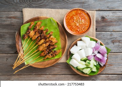 Overhead view Malaysian chicken satay with delicious peanut sauce, ketupat, onion and cucumber on wooden dining table, one of famous local dishes.