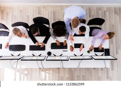 Overhead View Of Male Manager Discussing With Colleague Working On Computer