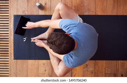 Overhead View Of Man Sitting On Exercise Mat Using Digital Tablet