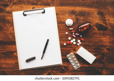 Overhead view of medical doctor office desk with note pad clipboard and prescription drugs