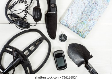 Overhead view of metal detector accessories placed on white wooden table. Items included metal detector, shovel, knife, gps, compass, map and headphones. Treasure hunters concept.