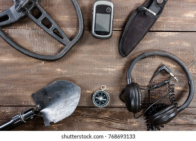 Overhead view of metal detector accessories placed on rustic wooden table. Items included metal detector, shovel, knife, gps, compass and headphones. Treasure hunters concept.