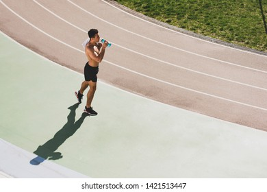 overhead view of mixed race sportsman holding towel and drinking water at stadium