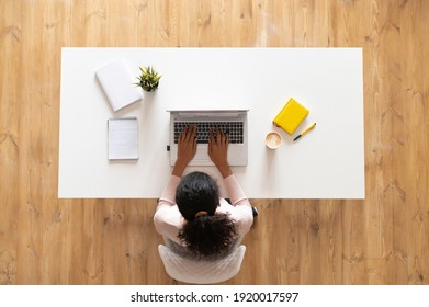 Overhead view of mixed-race ethnic woman or female freelancer with curly hair sitting at the white table desk with well-organized space, typing on the laptop, taking notes, modern home office concept