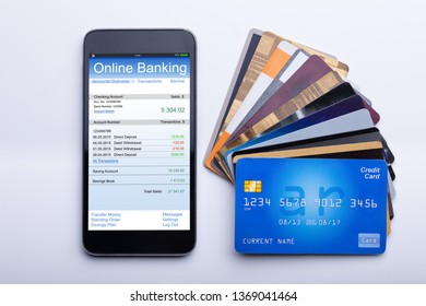 An Overhead View Of Mobilephone With Online Banking App And Credit Cards On White Desk