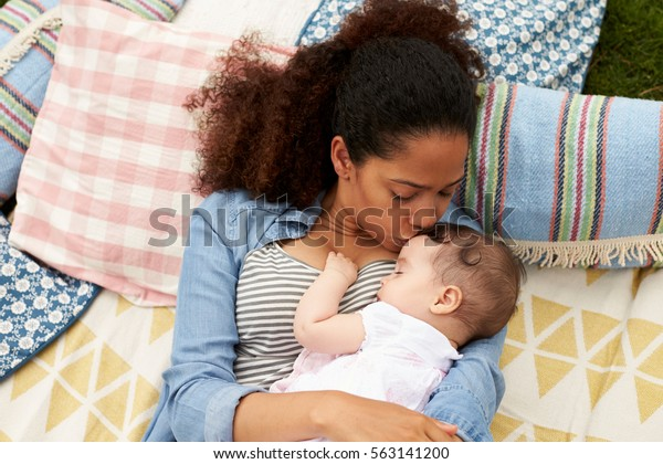 Overhead View Of Mother With Baby Relaxing On Rug In Garden