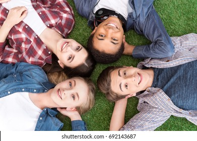 overhead view of multiethnic group of smiling teenagers lying on green lawn and looking at camera