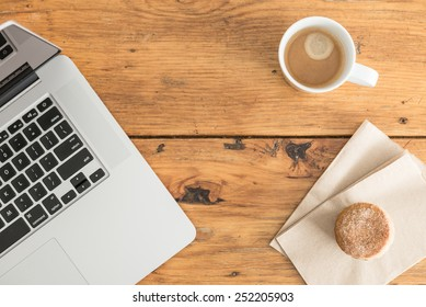 Overhead view of a notebook computer, fresh muffin and a white cup of coffee on a rustic wooden cafe table.