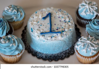 overhead view of number one on birthday cake with cupcakes in a winter theme