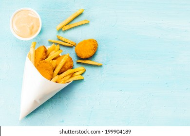 Overhead view on a blue background with copyspace of medallions of fried fish and chips in a takeaway paper cone with savory mayonnaise dip