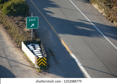 Overhead view on an exit sign along a freeway offramp, in a transportation background