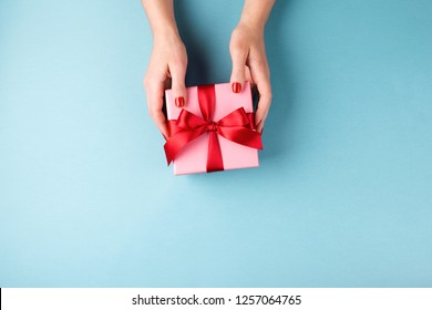 Overhead view on female hands holding pink gift box wrapped with red bow on blue background. Minimal styled composition.