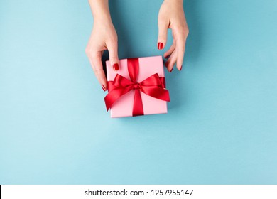 Overhead view on female hands with pink gift box wrapped with red bow on blue background. Minimal styled composition.