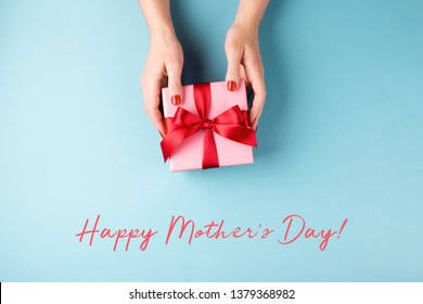 Overhead view on female's hands holding pink gift box wrapped with red bow on blue background. Minimal styled composition. Happy mother's day greeting card.