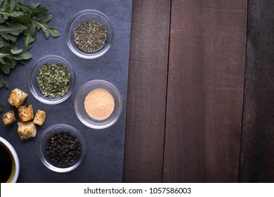 Overhead view on glass ingredient dishes with garlic and Italian herb spices on a gray slate, with a dark wood table background