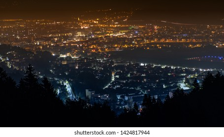 Overhead view of a orange and blue city at night. Mountain top overlooking Innsbruck