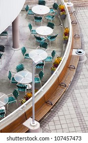 Overhead view of an outdoor city cafe or restaurant.  Top view, looking down onto tables, chairs and architecture.