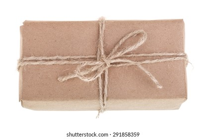 Overhead view of a package wrapped with plain brown paper and tied with string isolated on white