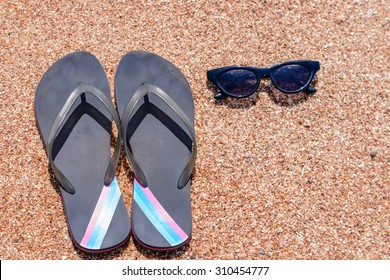 5c79f0bdfe9a8 Overhead view of a pair of slip slops and sunglasses on a beach neatly laid  out
