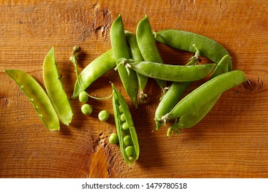 Overhead view of peas in pods on wooden background. Health eating concept. Homegrown food. Copy space